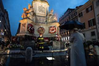 Pope Francis prays at the base of a tall Marian statue overlooking the Spanish Steps in Rome Dec. 8, 2002, the feast of the Immaculate Conception. The pope prayed at the statue shortly before the Rome firefighters' traditional early morning event in honor of the Immaculate Conception.