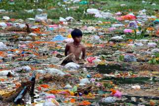 In this Sept. 9, 2014, file photo, a young man collects items on Jawahar Lal Nehru Lake after a festival in Bhopal, India. Some doctors say patients have a right to have causes of illness, especially from environmental pollution, studied as part of their care.