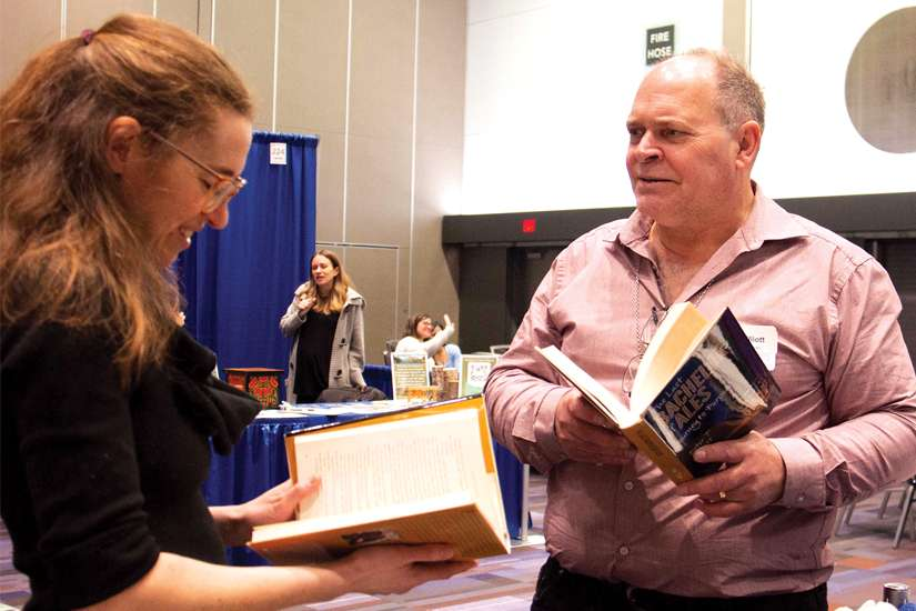 Peter Elliott browses books with fellow Catholic author Anna Eastland at the Catholic Educators' Conference last month.