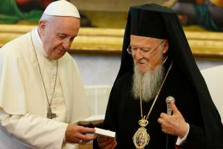 Pope Francis presents a gift to Ecumenical Patriarch Bartholomew of Constantinople during a meeting in the Apostolic Palace at the Vatican May 26.