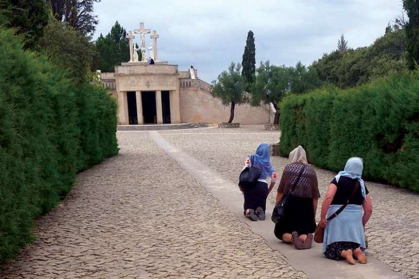 Pilgrims pray before the Fatima Shrine in Fatima, Portugal. The World Rosary Campaign is collecting prayers for world peace to promote the Fatima message on a global scale.