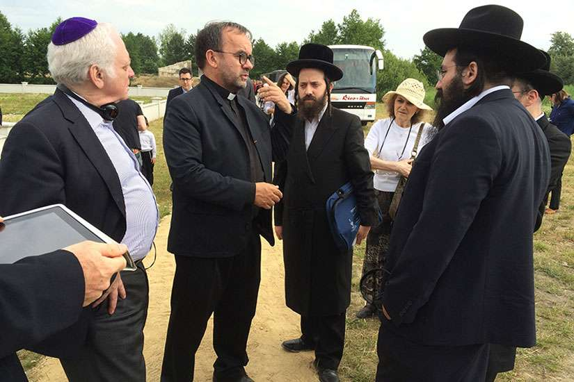 Fr. Patrick Desbois, second from left, greets visitors at the Rava-Ruska Holocaust mass grave on June 29, 2015. Desbois found and documented more than 1,600 Jewish mass graves in Ukraine and elsewhere in Eastern Europe.