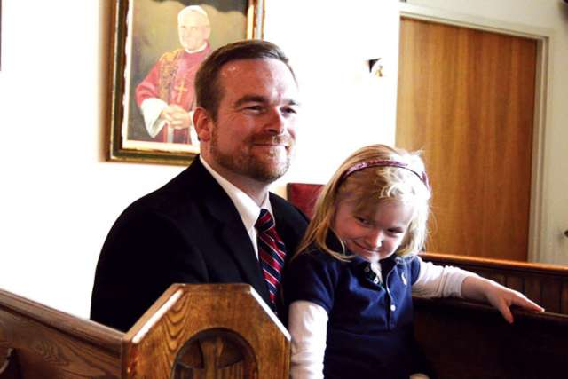 Mark Siolek, chaplain at Msgr. Percy Johnson Catholic High School, with his daughter, Madeline, sits in the pews he salvaged for the school chapel.