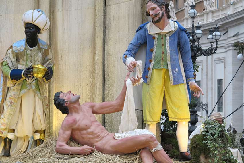 Life-size statues depict the corporal work of mercy of clothing the naked in the Nativity scene in St. Peter's Square at the Vatican Dec. 14.
