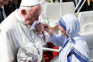 Pope Francis kisses a prayer card presented by a Missionaries of Charity nun at the conclusion of the canonization Mass of St. Teresa of Kolkata in St. Peter's Square at the Vatican Sept. 4.