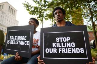 "People gather to remember all victims of police violence during a rally outside City Hall in Baltimore July 27. Baltimore's archbishop William E. Lori called a recently released report by the U.S. Department of Justice on the systemic abuses by the city's police ""sobering and distressing."""