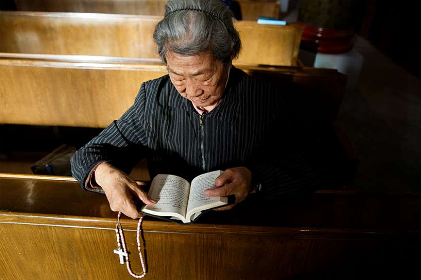 A woman holding a rosary prays Oct. 1 at St. Joseph Catholic Church in Beijing.