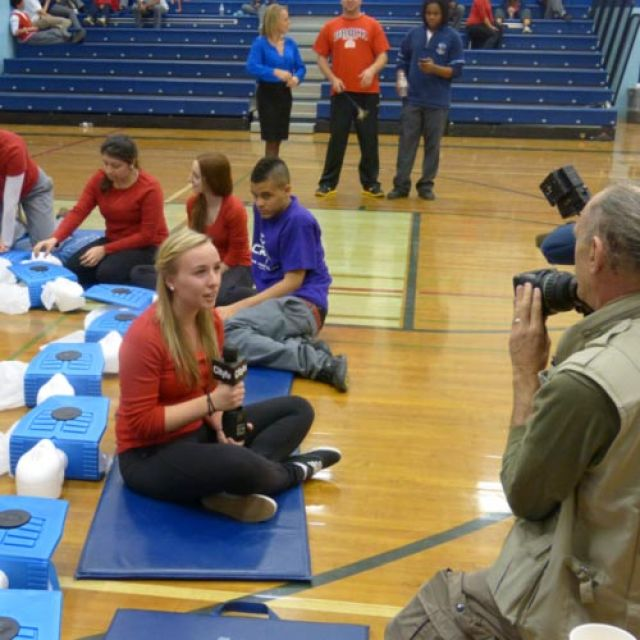 Cardinal Leger Secondary School student Paris Dickinson is interviewed by a TV station as the students in background continue with the CPR world record attempt.