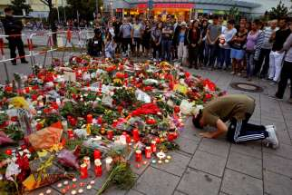 A man prays outside the Olympia shopping mall in Munich, Germany, July 23, where nine people were killed by an 18-year-old gunman.