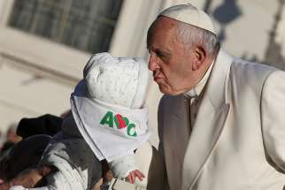 Pope Francis kisses a baby as he arrives for his general audience Jan. 24 in St. Peter's Square at the Vatican.