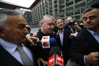 Father John O'Reilly, center, of the Legionaries of Christ arrives at a court in Santiago, Chile, Oct. 15. The court found Father O'Reilly, who moved to Chile from Ireland in 1985, guilty of sexually abusing a pre-teen girl at the private Colegio Cumbres in the affluent neighborhood of Las Condes between 2007 and 2009.