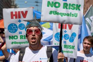 Participants march July 23 through the streets of Amsterdam, marking the opening of the 2018 International AIDS Conference. The man carries a sign supporting the belief that HIV-positive individuals with an undetectable viral load for six month are not contagious to others.