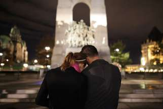 A couple embraces at the foot of the National War Memorial in Ottawa, Ontario, Oct. 23. Cpl. Nathan Cirillo, a Canadian soldier, was shot and killed the previous day while on duty at the nearby National War Memorial.
