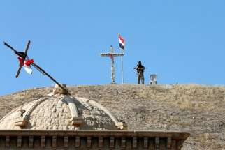 An Iraqi soldier guards St. Barbara Church Oct. 30 after it was recaptured from Islamic State militants in Qaraqosh. Similarly, in the town of Bashiqa, north of Mosul, the Mar Korkeis church was reopened after two years under Islamic State control.