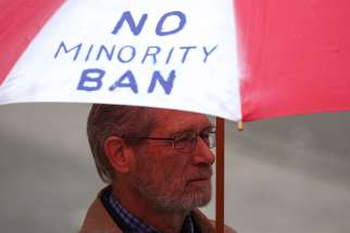 A man holds an umbrella during a protest in Seattle May 15 against President Donald Trump's travel ban. The U.S. Court of Appeals for the 4th Circuit, based in Virginia, issued a 10-3 ruling May 25 to uphold a Maryland federal court's injunction against the temporary ban.