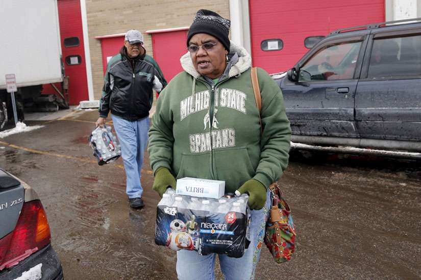 Flint resident Ruby Adolph carries bottled water and a replacement water filter she received at a fire station in Flint, Mich., on Jan. 13, 2016.