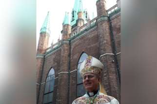 Bishop Ronald Fabbro in front of Our Lady of the Assumption church in Windsor.