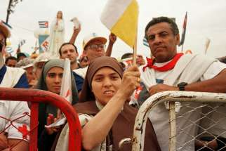 A nun waves a Vatican flag while attending Mass with Pope John Paul II in Havana Jan. 25, 1998. During his five-day visit to Cuba, the pope called for a spiritual renewal among the Cuban people.