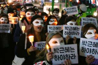 "South Korean university students carry candles and placards that read ""Park Geun-Hye Step Down"" Nov. 15 in Seoul. The South Korean president is embroiled in scandal involving a longtime friend."