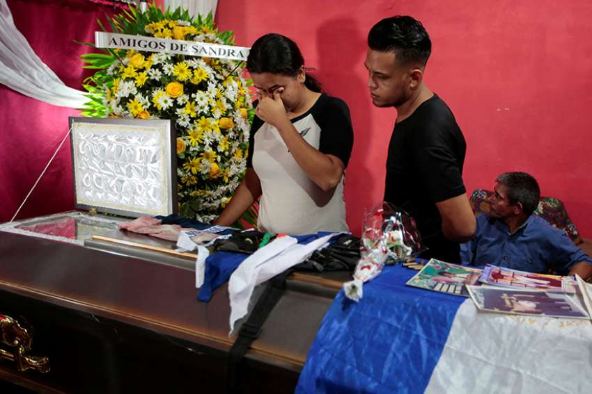 Young people mourn over the casket of Gerald Jose Vasquez, a student at the National Autonomous University of Nicaragua, during his July 15 wake in Managua. Vasquez was one of two students shot and killed by paramilitary forces when they were seeking refuge in Divine Mercy Catholic Church after being forced from the university they had occupied in protest for more than two months.