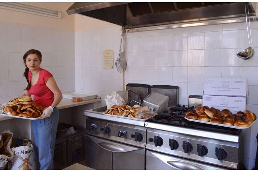 Graziana Pistorio, a volunteer, prepares food donated by local bakeries at the Caritas centre in Catania, Sicily.