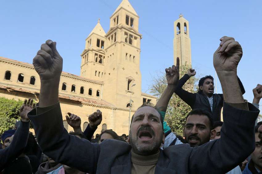 Christians chant anti-terrorism slogans outside the Coptic Orthodox cathedral complex Dec. 11 after an explosion inside the complex in Cairo.