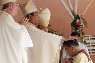 Cardinal-designate Louis-Marie Ling Mangkhanekhoun, apostolic vicar of Pakse, Laos, places his hands on a new bishop during a 2010 ordination Mass. Cardinal-designate Ling is one of five new cardinals Pope Francis will create at a June 28 consistory.