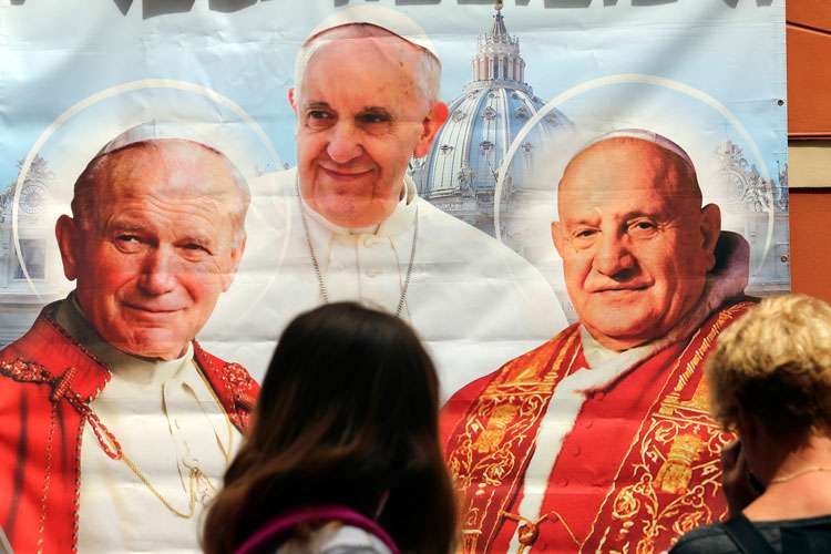 A woman takes a picture of an illustration depicting Blessed John Paul II, left, Pope Francis and Blessed John XXIII outside a shop in Rome April 23.  Pope Francis expressed his hopes that the two soon-to-be saints would continue to inspire the whole church in its mission.