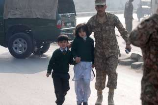 A soldier escorts schoolchildren from the Army Public School in Peshawar, Pakistan, Dec. 16, 2014. Archbishop Sebastian Shaw of Lahore says the increased security around Catholics schools are, psychologically, making children feel unsafe.