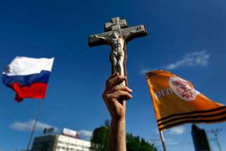 A pro-Russian man holds a crucifix next to a Russian flag during a demonstration in Donetsk's Lenin Square May 24 against the Ukrainian elections. Bishop Marian Buczek said church members are afraid to attend Mass in Donetsk and other towns after a priest was abducted by pro-Russia separatists.