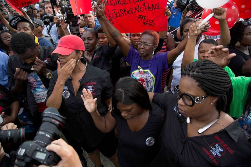 Community members attend a July 7 vigil in memory of Alton Sterling, who was shot dead by police outside a market in Baton Rouge, La. Sterling, 37, was killed early July 5 in a shooting that was captured on cellphone video.
