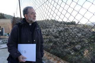 Bishop Lionel Gendron of Saint-Jean-Longueuil, Quebec, looks through a fence at the Cremisan Valley from the Salesian Sisters' convent in Beit Jalla, West Bank, Jan. 13. Bishop Gendron is part of the Holy Land Coordination visit for bishops from Europe and North America.