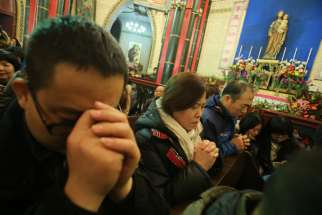 People pray during Mass at a Catholic church in Beijing in 2014.