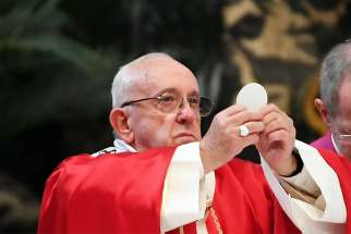 Pope Francis elevates the Eucharist during a Mass for deceased cardinals and bishops in St. Peter's Basilica at the Vatican Nov. 3.