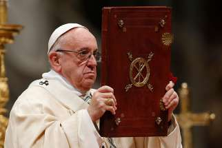 Pope Francis raises the Book of the Gospels during a Mass marking the feast of the Epiphany in St. Peter's Basilica at the Vatican Jan. 6.