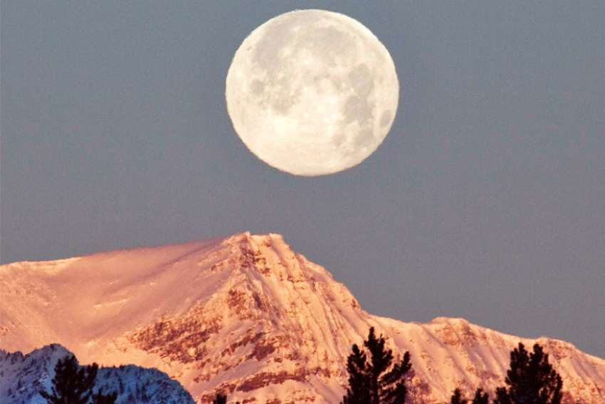 The moon sets behind a mountain at sunrise in Lake Louise, Alta.