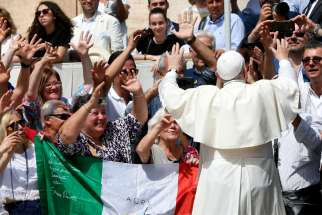Pope Francis uses sign language in response to a group of people using sign language during his general audience in St. Peter's Square at the Vatican June 12, 2019.