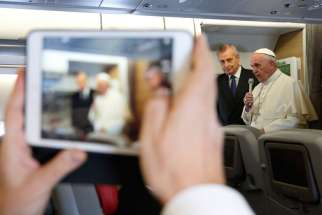 A journalist takes a photo on a tablet as Pope Francis speaks to journalists aboard his flight from Rome to Nairobi, Kenya, Nov. 25. The pope is visiting Kenya, Uganda and the Central African Republic during his six-day African tour.