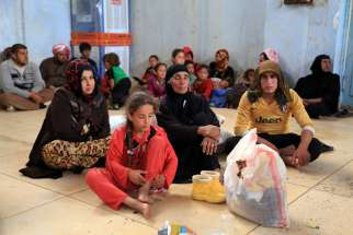 Displaced families await temporary shelter in Kirkuk, Iraq, June 11. Catholic and Orthodox patriarchs called for the rapid liberation of areas under control of the Islamic State group to end ethnic and religious genocide.