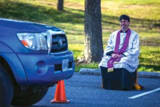 Fr. Scott Holmer, a pastor in Bowie, Md., offers drive-through confessions in the parking lot of his parish church, keeping a safe distance away from penitents amid the coronavirus pandemic.