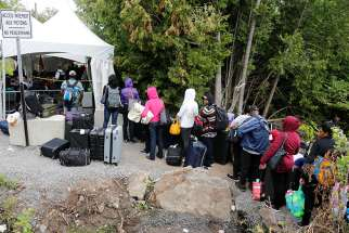 A group of Haitians wait to cross the U.S.-Canada border into Quebec from New York in late August.