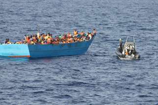 The Irish Naval Service approach a boat filled with migrants Oct. 21, 2016 in the Mediterranean Sea off the coast of Tripoli, Libya. 245 were feared dead or missing from two shipwrecks in the Mediterranean Sea over the weekend.