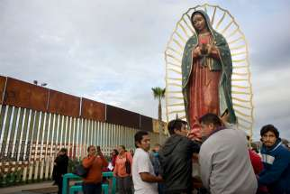 "A file photo shows a statue of Our Lady of Guadalupe as it is unloaded from a truck after a procession to the U.S.-Mexico border fence in Tijuana, Mexico, where Mass was celebrated. Pope Francis has asked Catholics to add ""Comfort of Migrants"" and two other titles for Mary to the popular ""Litany of Loreto."""