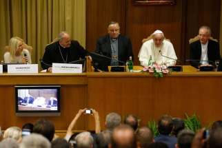 Pope Francis addresses a workshop on climate change and human trafficking attended by mayors from around the world in the synod hall at the Vatican July 21. Local government leaders were invited to the Vatican by the pontifical academies of sciences and social sciences to sign a declaration recognizing that climate change and extreme poverty are influenced by human activity. Also seen are, from left, Argentine model Valeria Mazza, serving as master of ceremonies; Bishop Marcelo Sanchez Sorondo, chancell or of the Pontifical Academy of Sciences; Cardinal Francesco Montenegro of Agrigento, Italy; and Cardinal Claudio Hummes, former prefect of the Congregation for the Clergy.