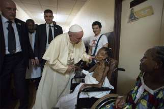Pope Francis greets a patient at a pediatric center in Bangui, Central African Republic, in this Nov. 29, 2015, file photo.