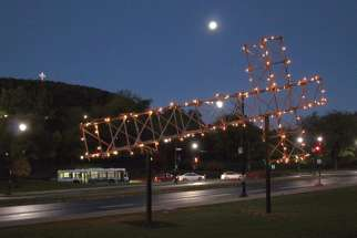 The fallen cross is lit up at night with Montreal's landmark cross atop Mount Royal in the background.