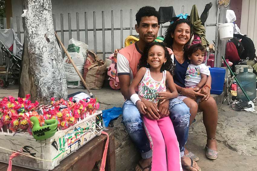 Venezuelan Roberto Sanchez, his wife and two young daughters pose for a photo in Cucuta, Colombia Feb. 9, 2019. The family lived at a Catholic-run shelter for the first two weeks, then moved out, only to be evicted by their landlord. Now they are living in the street and sell sweets to make a living, while they save up to rent a new place.