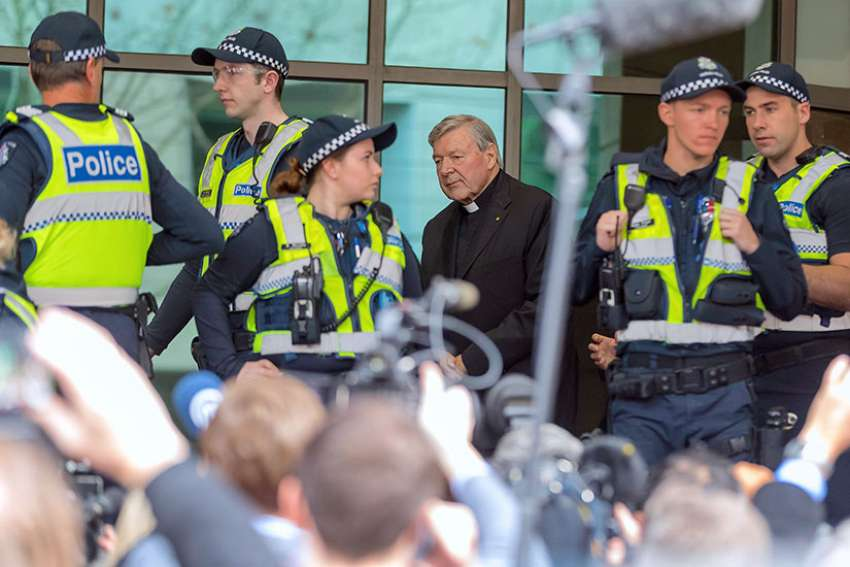 Vatican Treasurer Cardinal George Pell is surrounded by Australian police and members of the media as he leaves the Melbourne Magistrates Court in Australia on July 26, 2017.