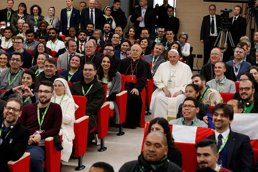Pope Francis poses for a photo at a pre-synod gathering of youth delegates at the Pontifical International Maria Mater Ecclesiae College in Rome March 19. The meeting was in preparation for the Synod of Bishops on young people, the faith and vocational discernment this October at the Vatican. Seated next to the pope are Cardinal Lorenzo Baldisseri, secretary-general of the Synod of Bishops, and U.S. Cardinal Kevin J. Farrell, prefect of the Vatican's Dicastery for Laity, Family and Life.