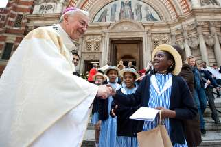 Cardinal Vincent Nichols of Westminster, England, greets Catholic school children outside Westminster Cathedral in London.